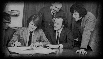 Carl signs the record deal.